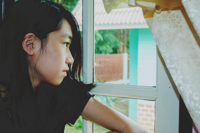 Image of girl looking out of window.